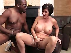 Big boobed mature brunette hungrily slurps massive black dong.